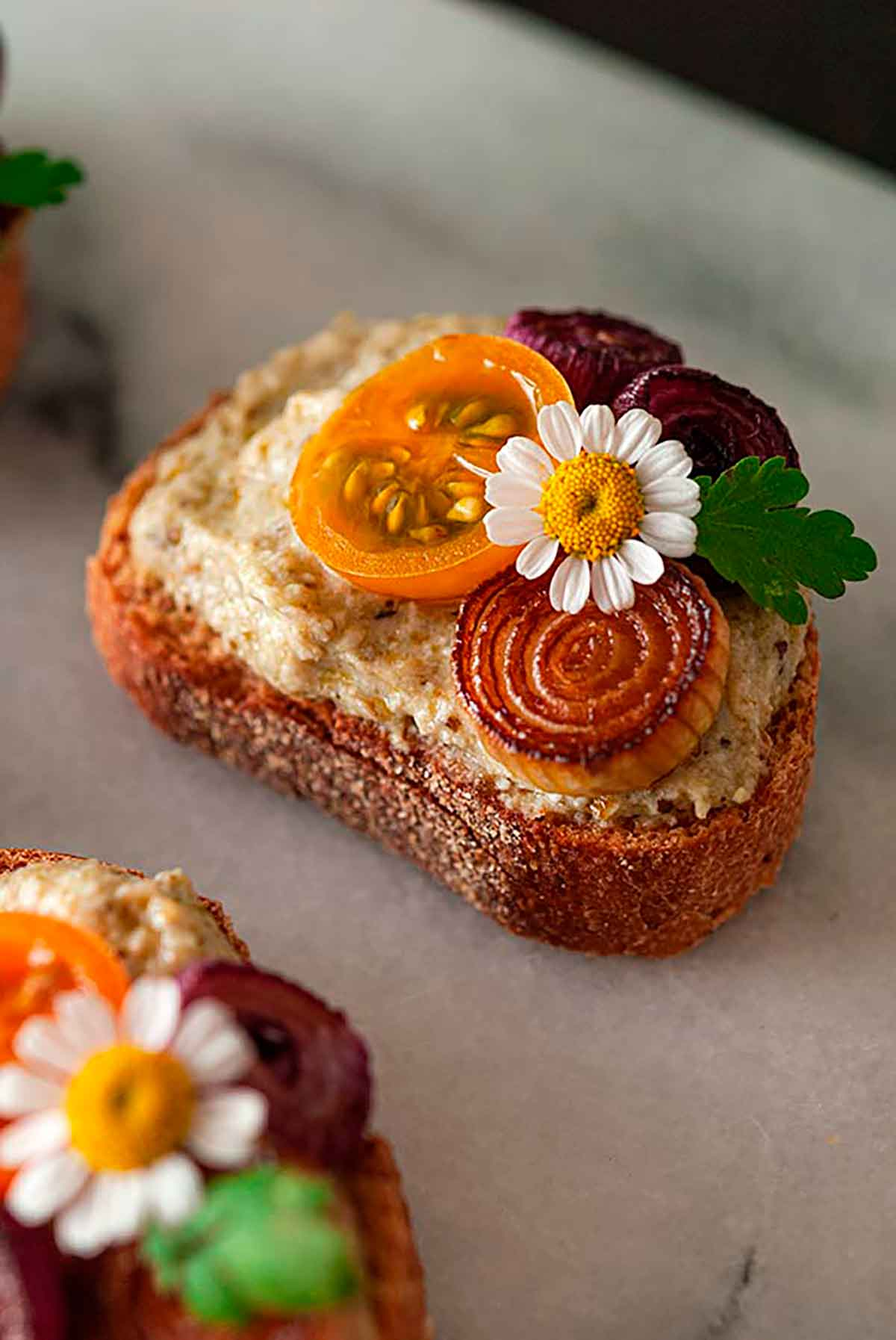 A pesto crostini with onions, tomato and small flower on a marble plate.