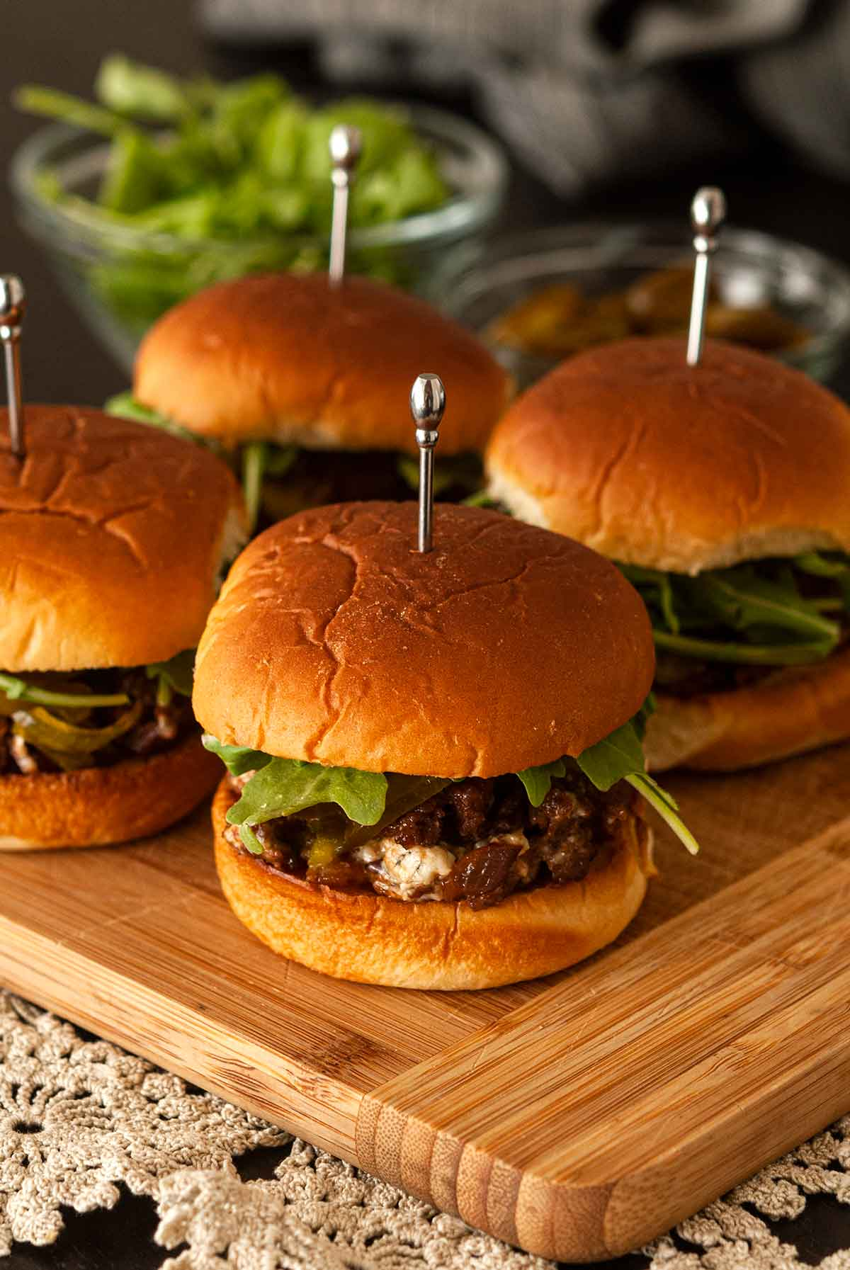 4 barbecue sliders on a cutting board above a lace table cloth with garnishes in the background.