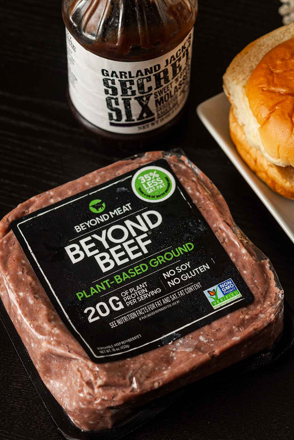 A package of Beyond Beef beside barbecue sauce and slider buns.
