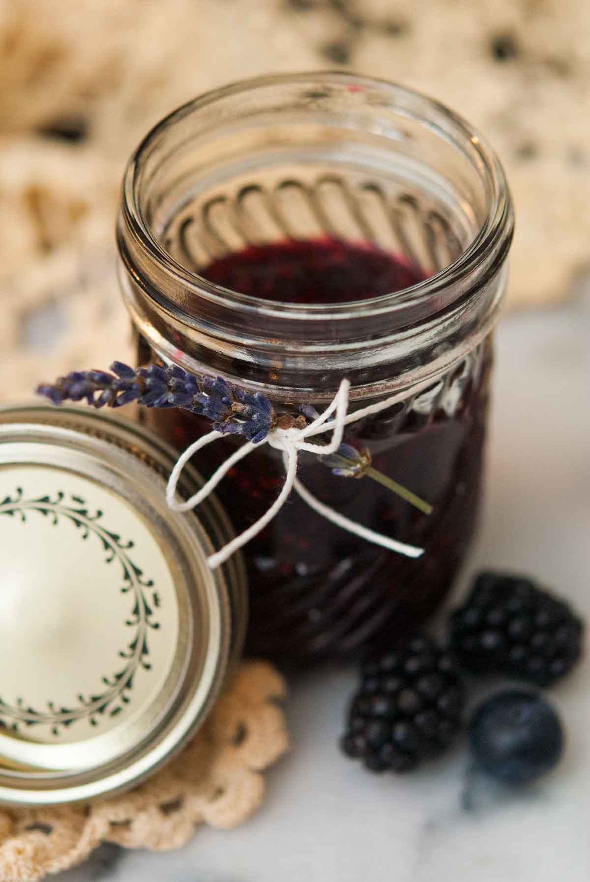 A jar of jam tied with a string with a sprig of lavender tucked into the string with a lace table cloth in the background.