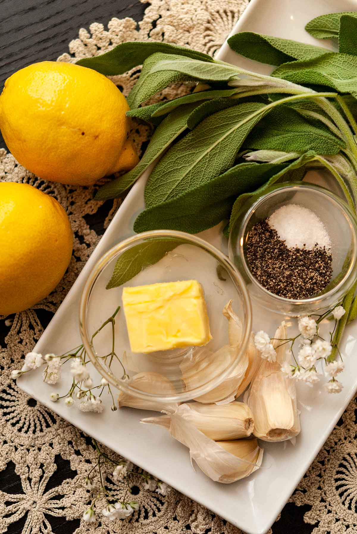 butter, garlic, spices, sage and lemons on a table cloth with a few scattered flowers.