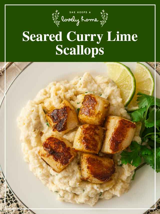 6 curry scallops on a plate with mashed cauliflower with parsley and lime slices for garnish.