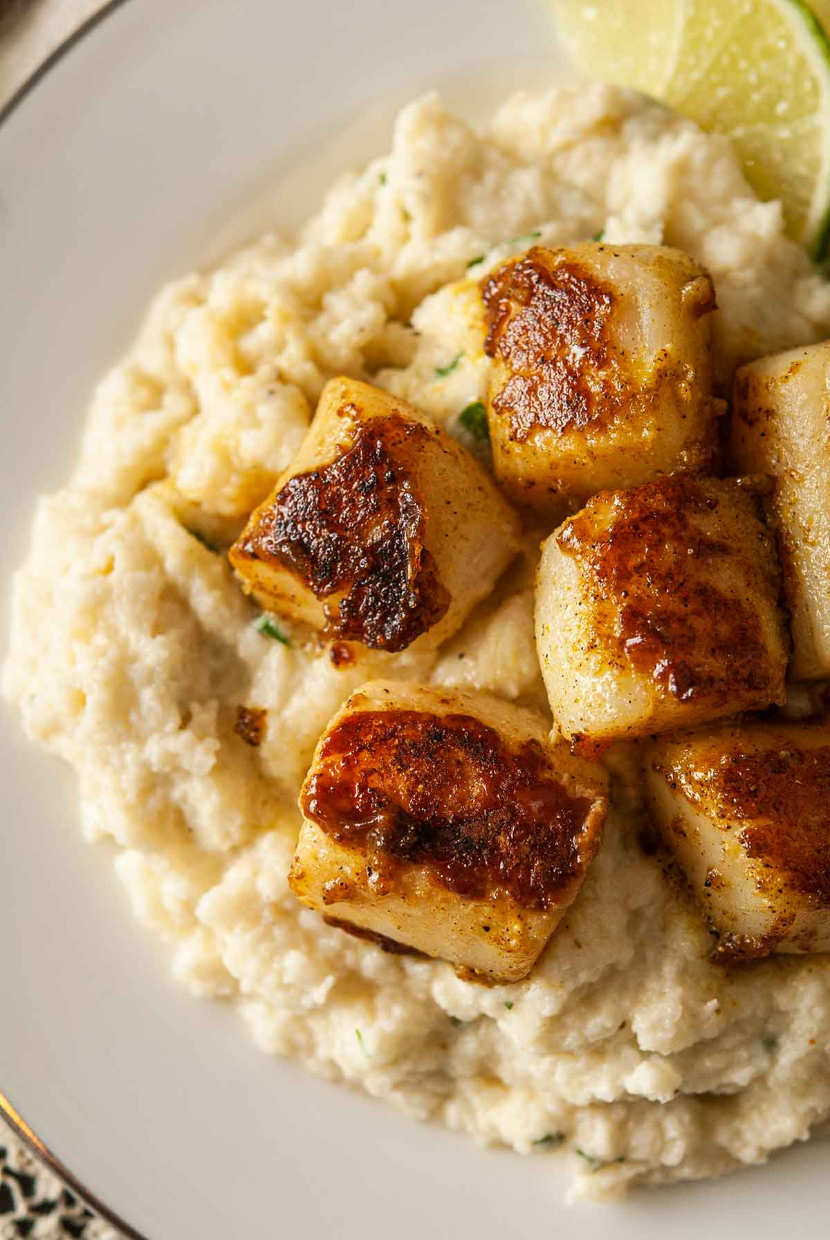 6 curry-seared scallops on a plate with mashed cauliflower.