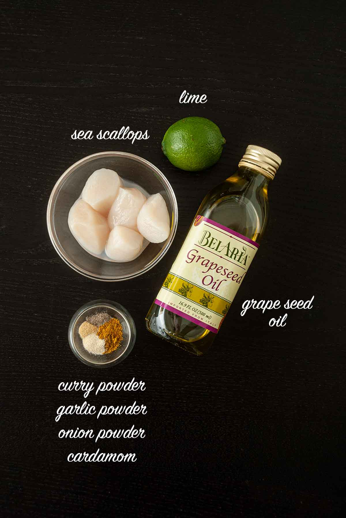 Ingredients for making curry scallops on a table with titles that describe what they are.