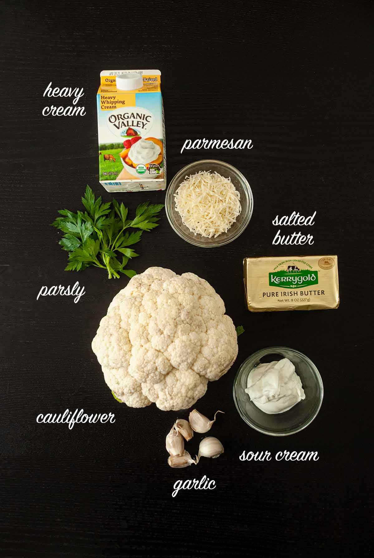 Ingredients on a table for making mashed cauliflower with titles that describe what they are.