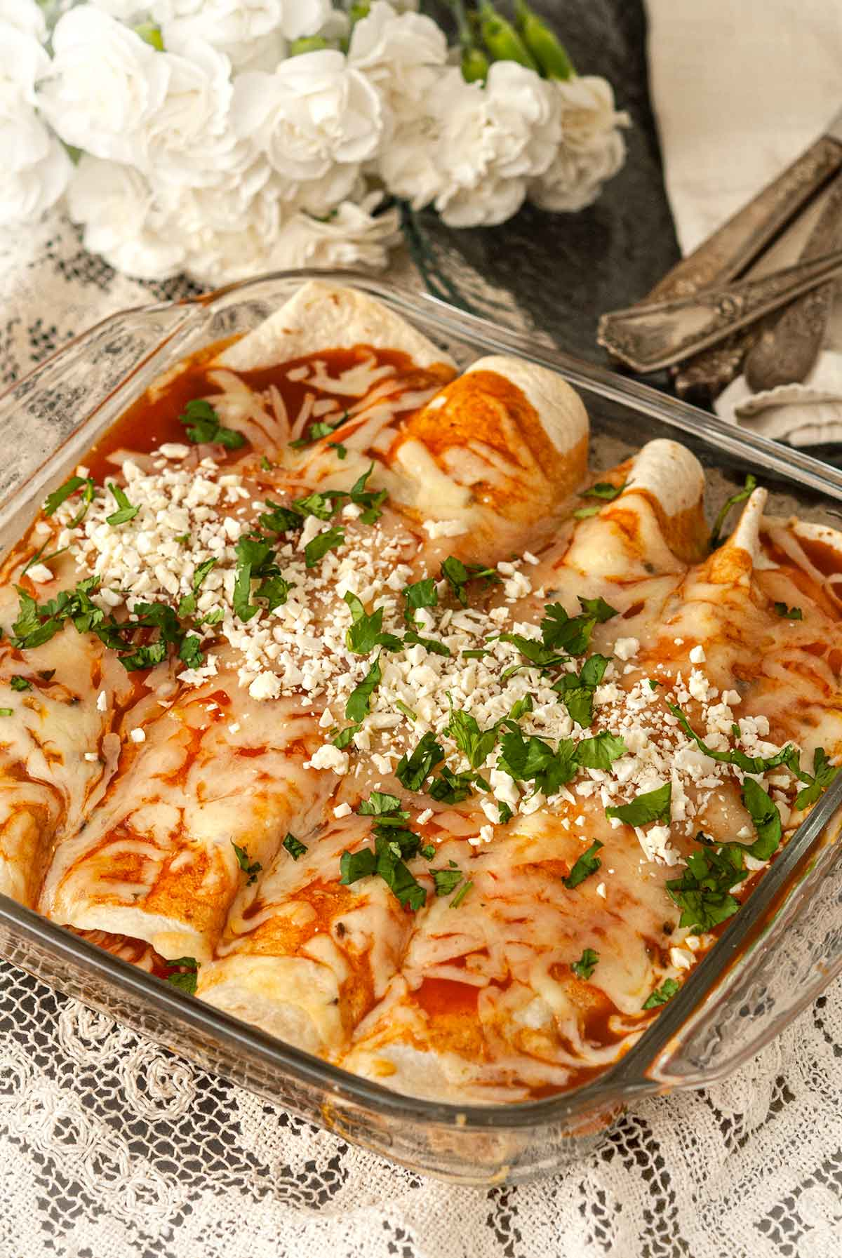 A Pyrex dish with 4 chicken enchiladas on a lace tablecloth with flowers and silverware in the background.