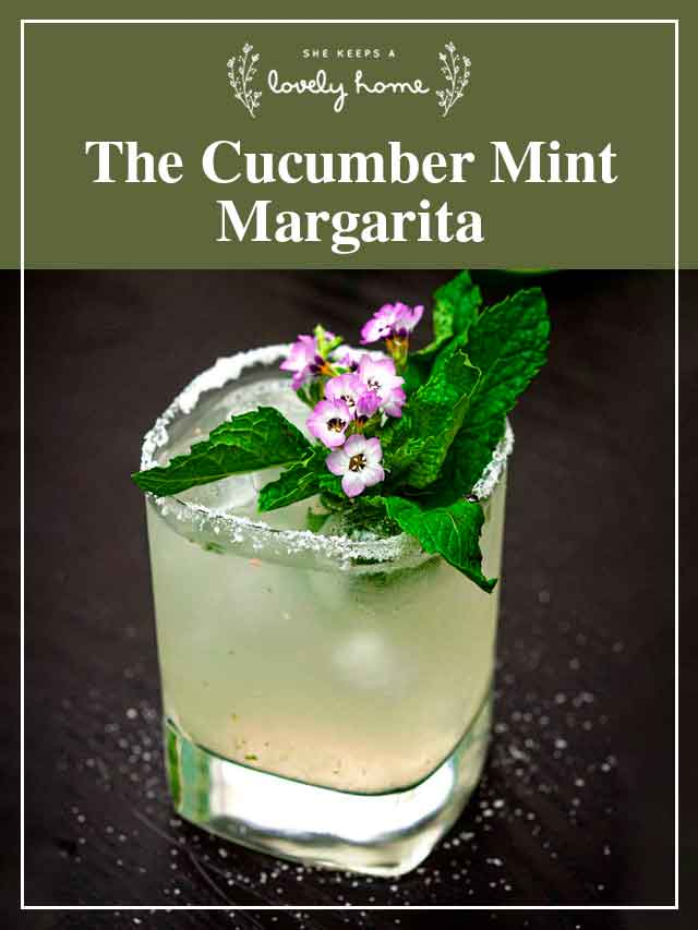 """A margarita garnished with flowers and mint with a title that says """"The Cumber Mint Margarita."""""""