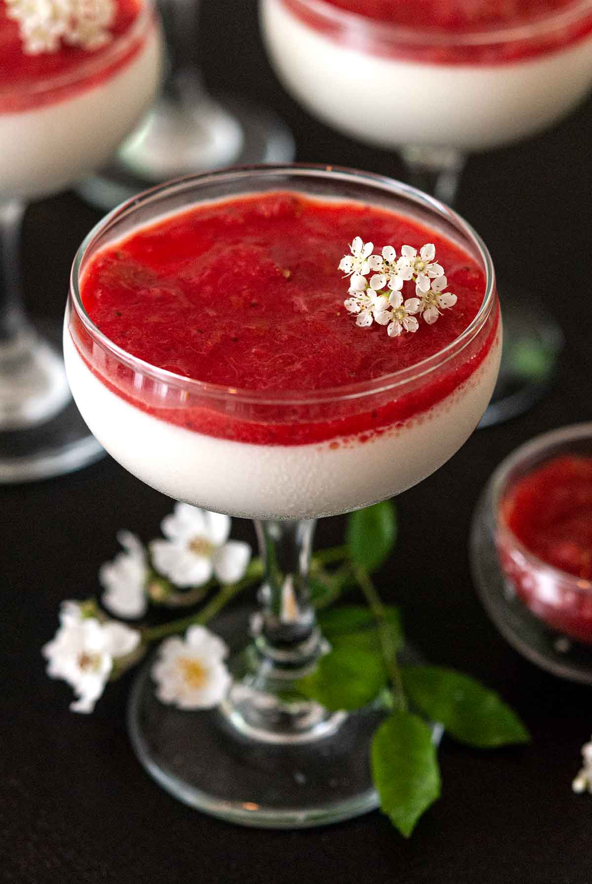 Panna cotta with strawberry-rhubarb compote in a glass, garnished with small flowers, in front of 2 others.