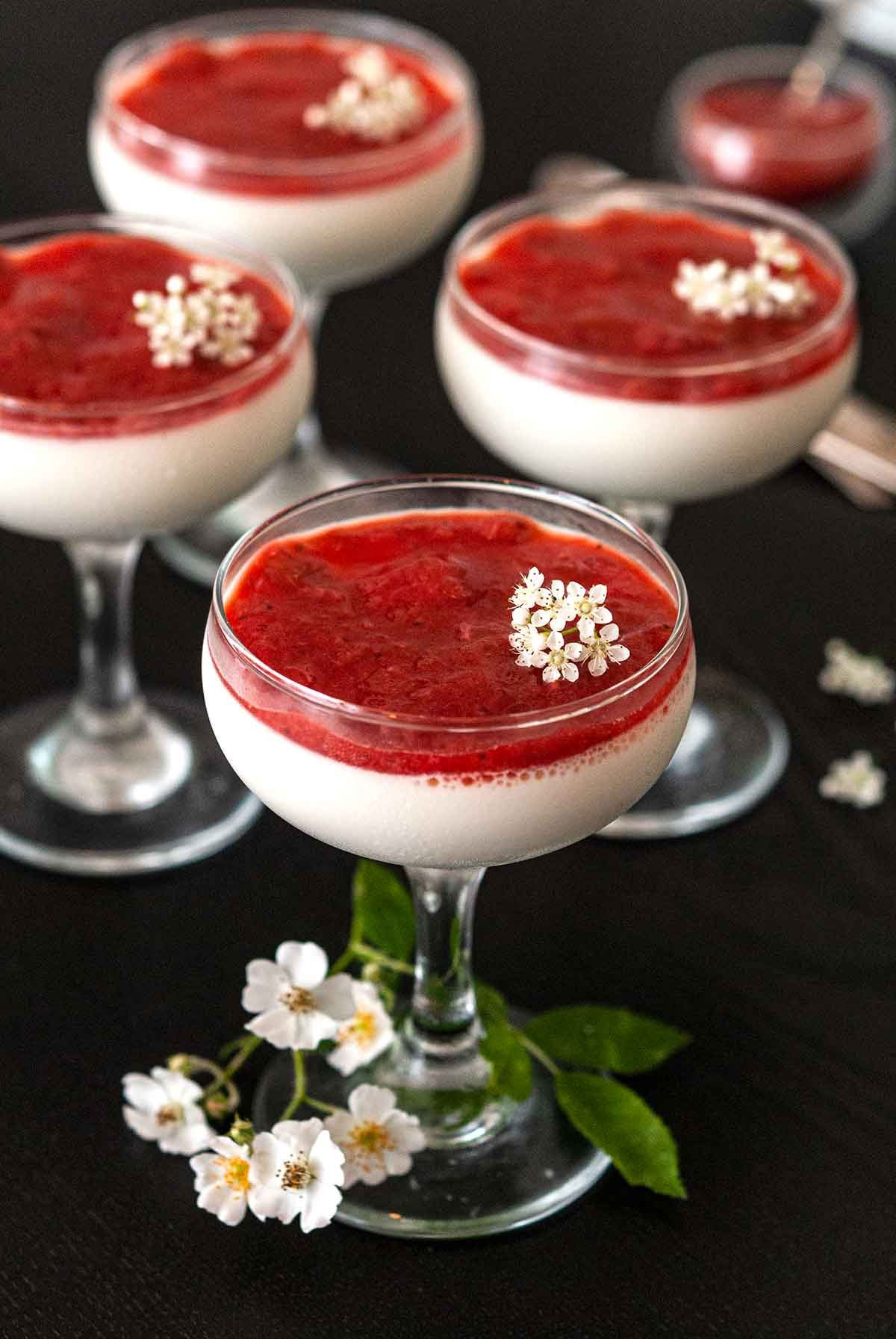 4 glasses of panna cotta with strawberry-rhubarb compote, garnished with flowers, on a table.