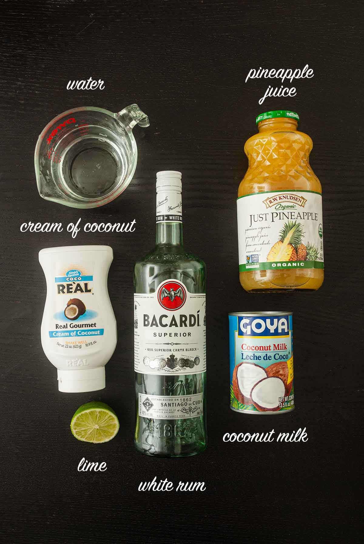 Ingredients for piña coladas on a table with titles.