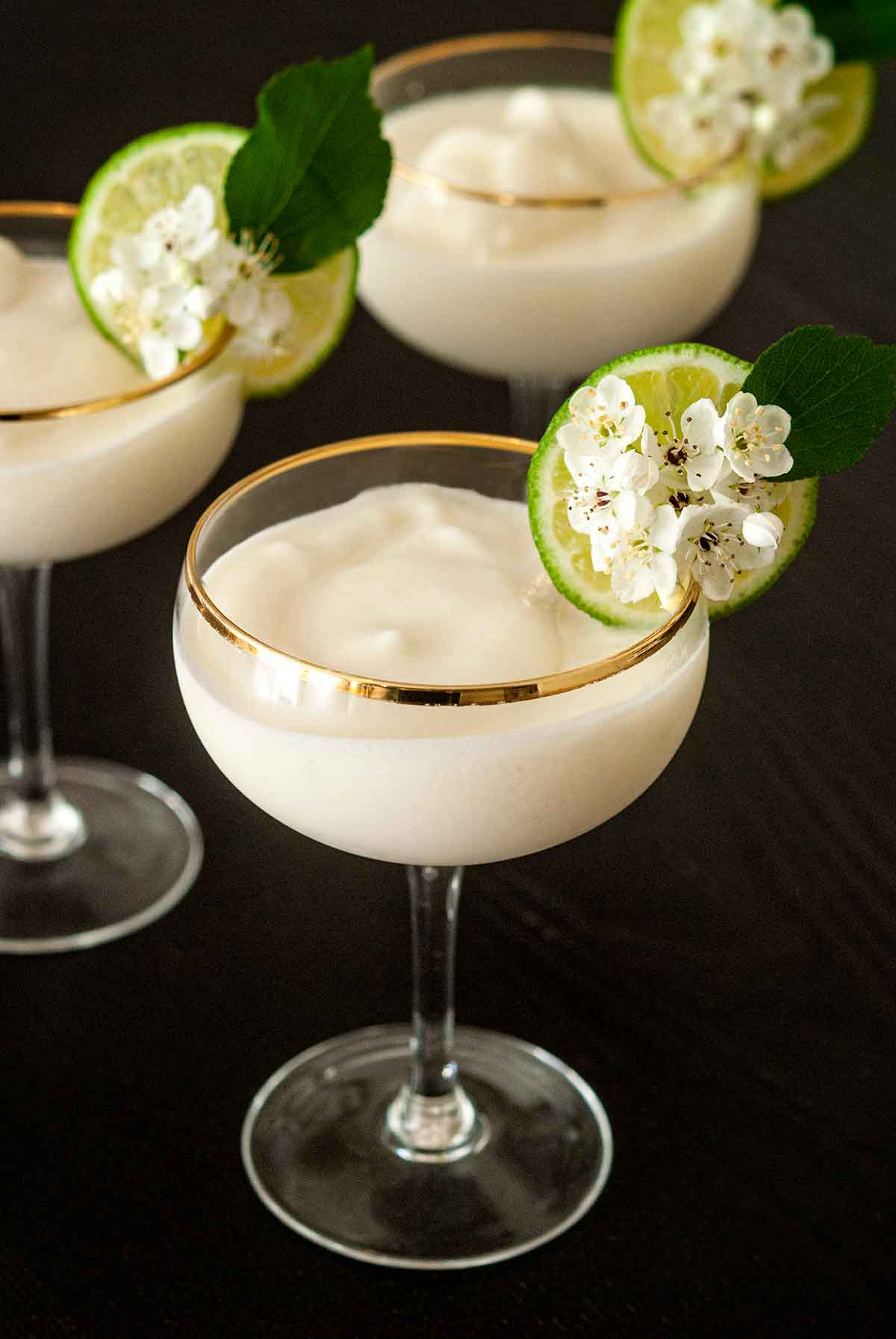 3 piña coladas in coup glasses, garnished with a lime and flowers on a table.