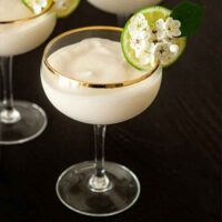 A piña colada in a coup glass, garnished with a lime and flowers.