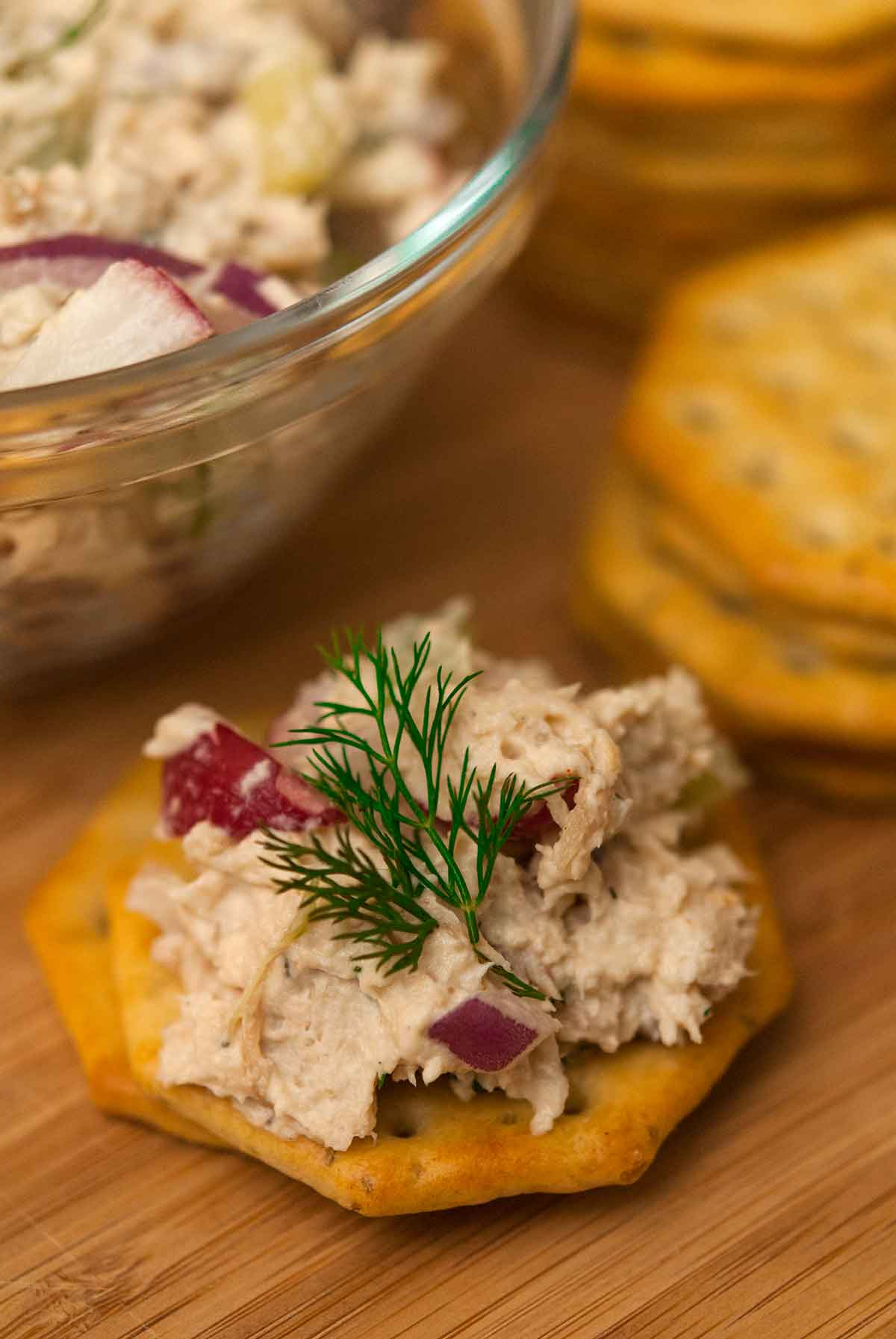 A cracker with chicken salad on a wooden plate.