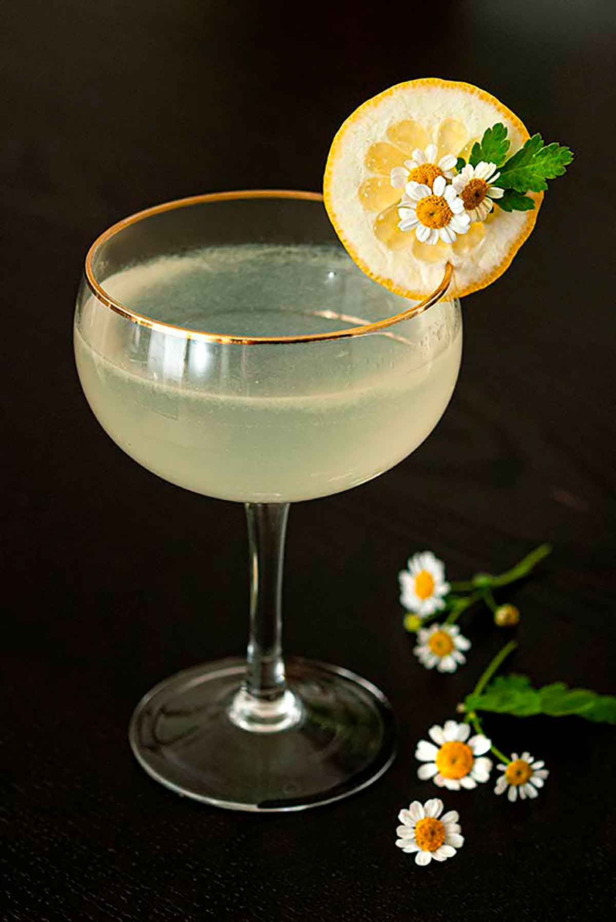 A Lemon Drop cocktail, garnished with a lemon slice and 3 small daisies on a table, with a bouquet in the background.