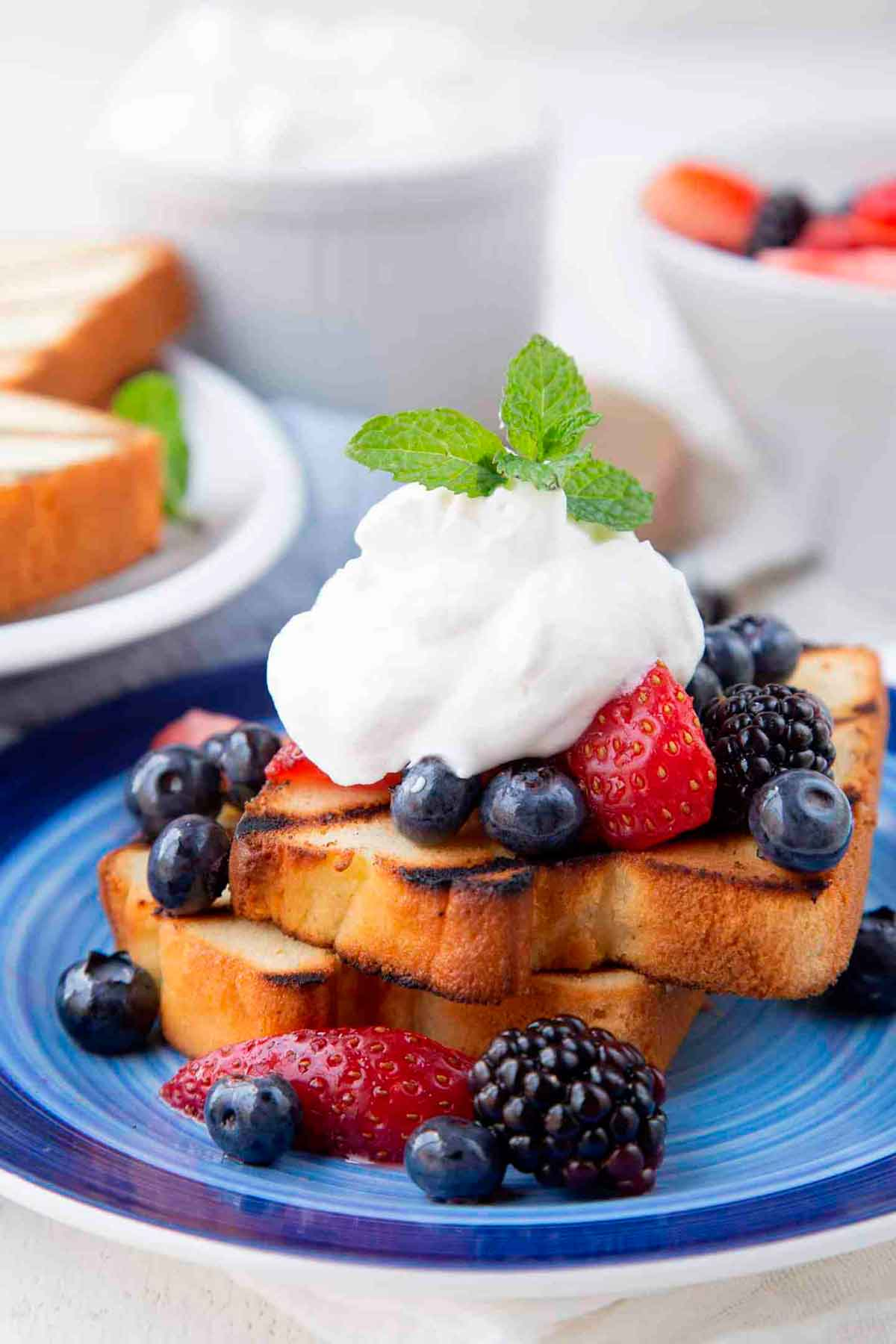 2 slices of pound cake, topped with berries and whipped cream on a plate.