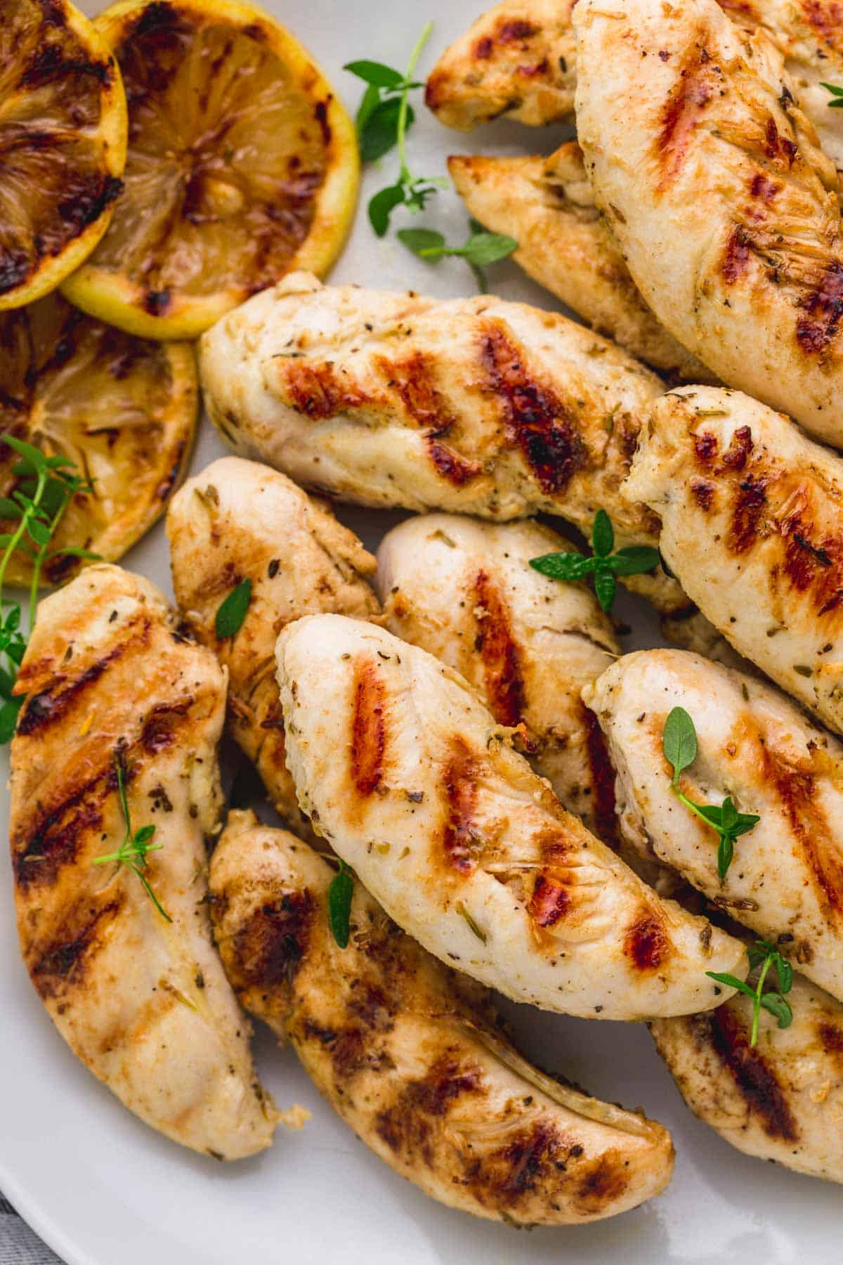 A plate of about a dozen grilled chicken tenders, sprinkled with thyme.