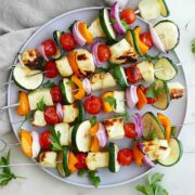 6 skewers on a plate with halumi and vegetables.