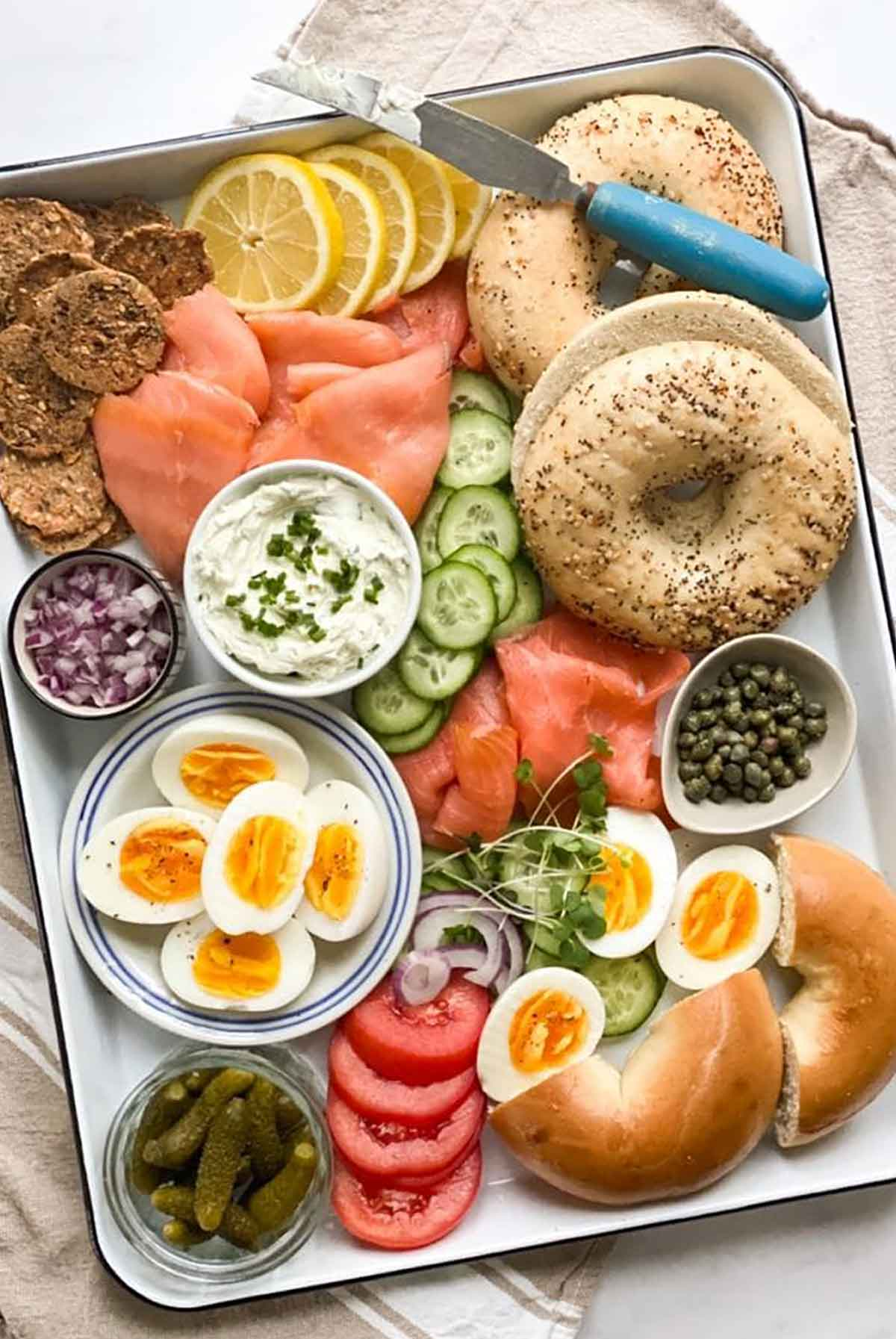 A tray of bagels with scattered, assorted bagel toppings.