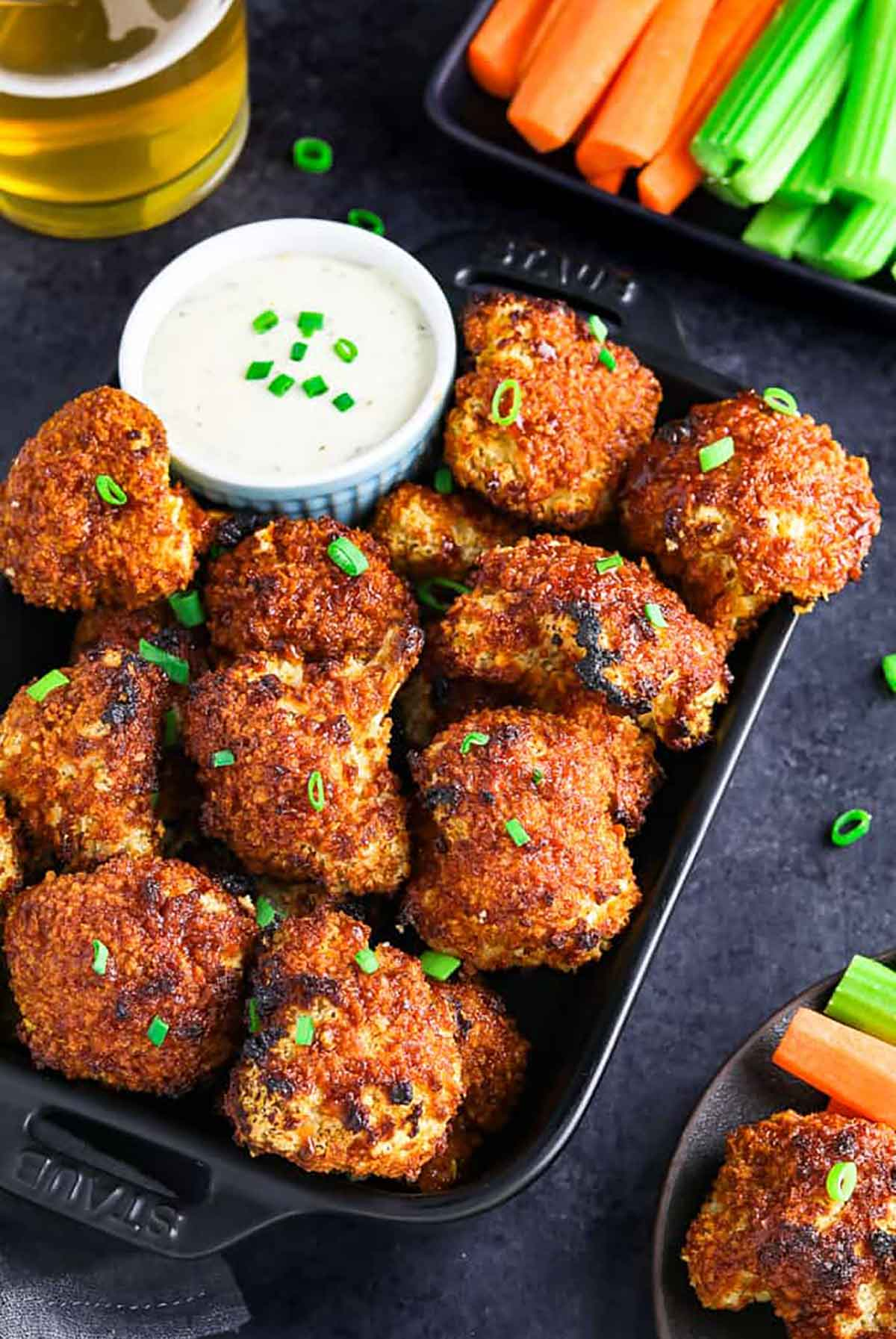 About a dozen cauliflower nuggets on a plate with a dipping sauce.