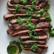 Sliced grilled steak on a plate with chimichurri sauce drizzled on top.