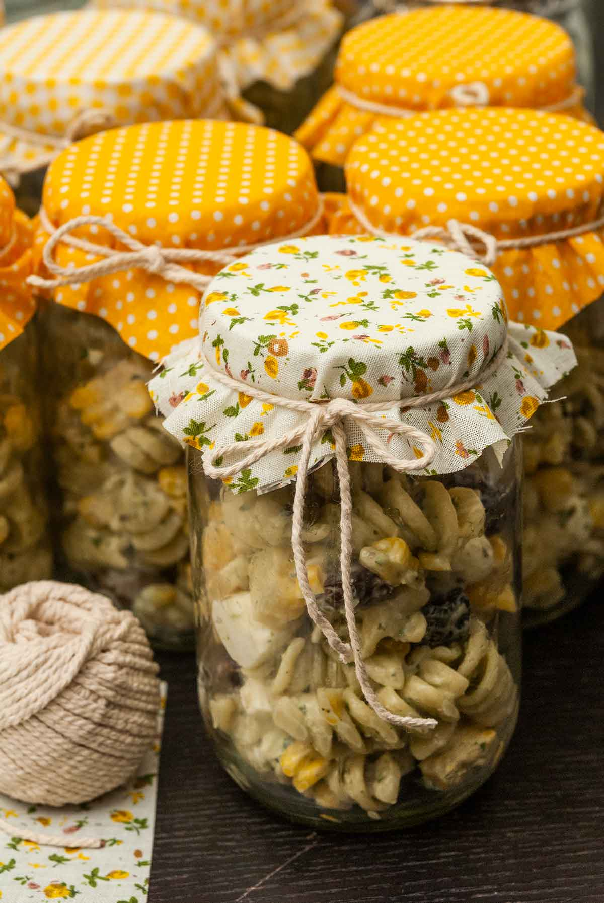 6 jars of pasta salad on a table, topped with fabric and tied with string.