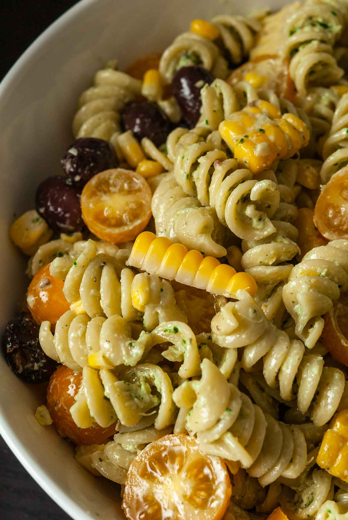 A bowl of pasta salad with fresh corn, tomatoes and olives.