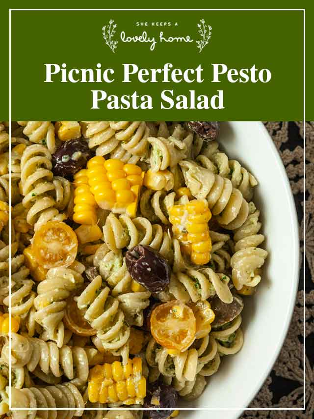 """Pasta salad in a bowl with a title that says """"Picnic Perfect Pesto Pasta Salad."""""""