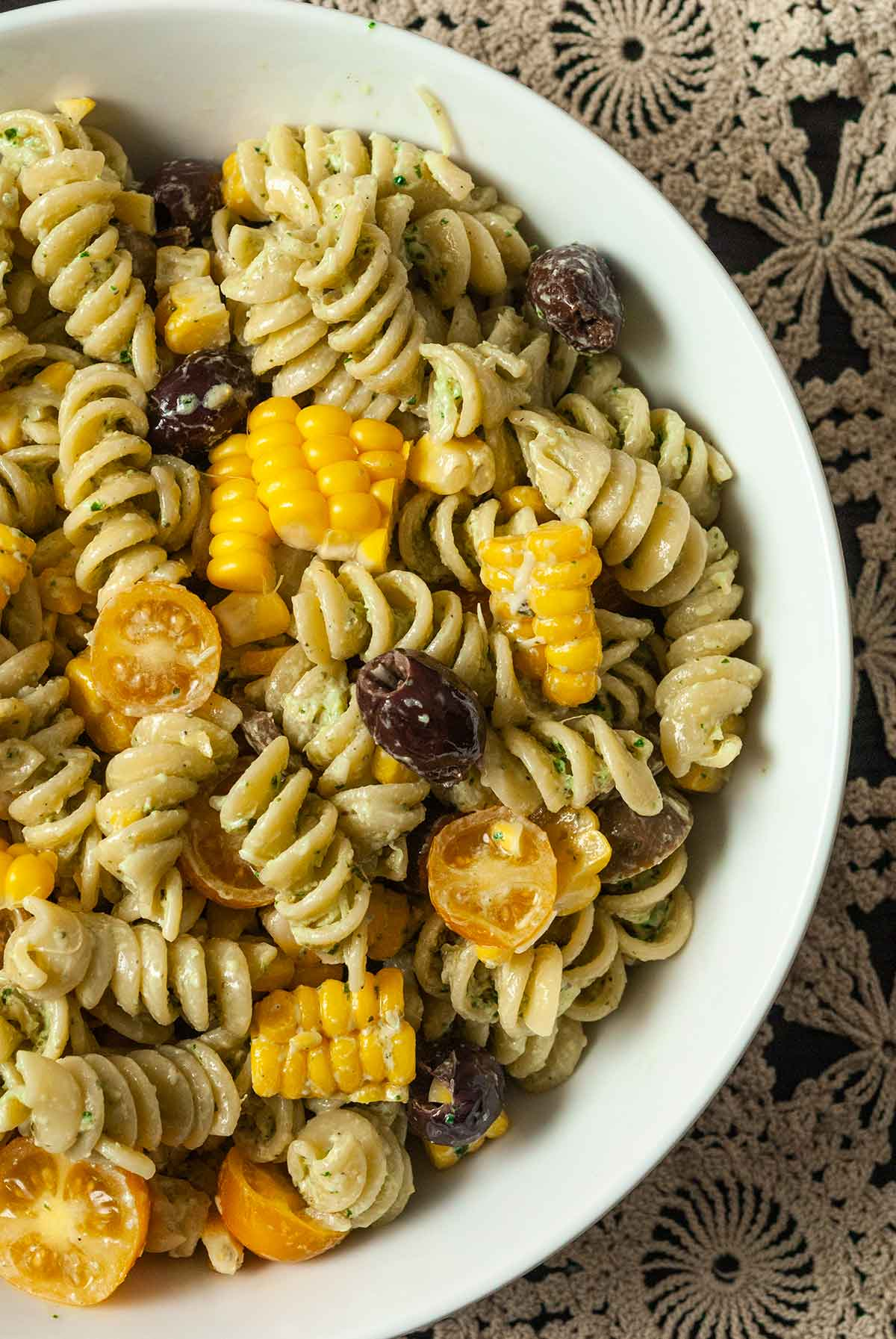 A bowl of pasta salad with fresh corn, tomatoes and olives on a lace tablecloth.