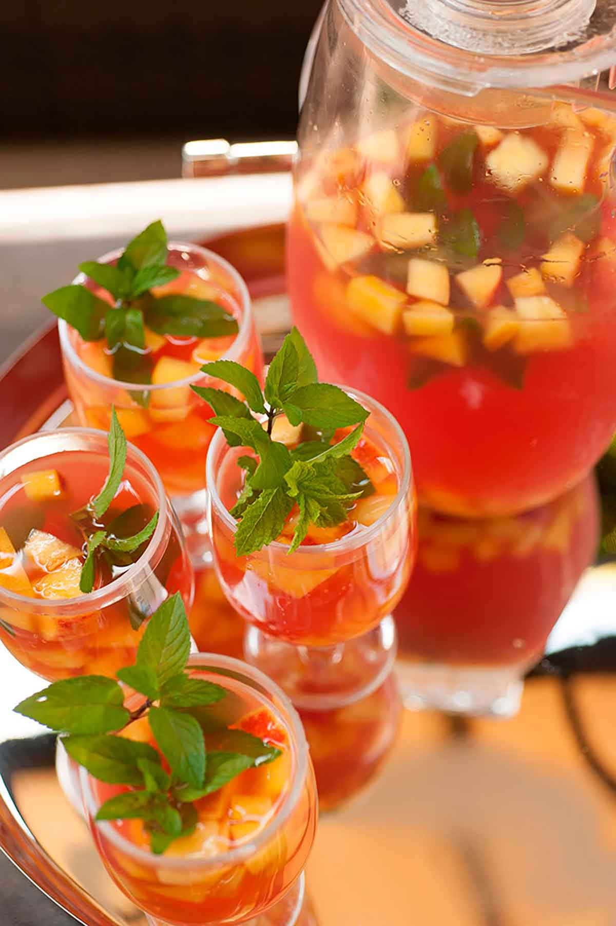 A silver tray with 4 glasses of fruit-filled watermelon sangria, garnished with mint, next to a full pitcher.