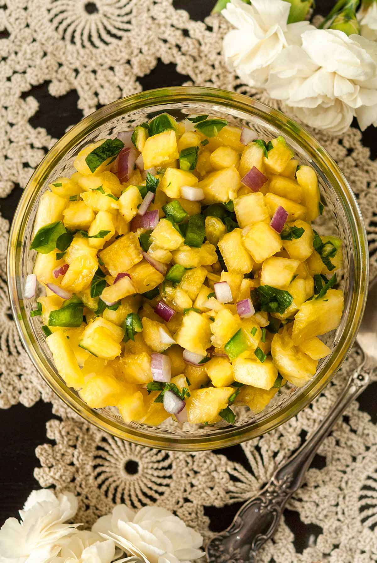 Pineapple jalapeño salsa in a small bowl on a lace tablecloth, beside a spoon and 2 small bunches of flowers.