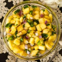 Pineapple jalapeño salsa in a small bowl on a lace tablecloth.