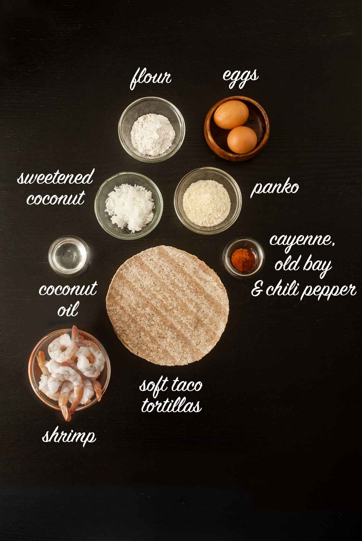 A number of ingredients for making coconut shrimp tacos on a table with titles describing what they are.