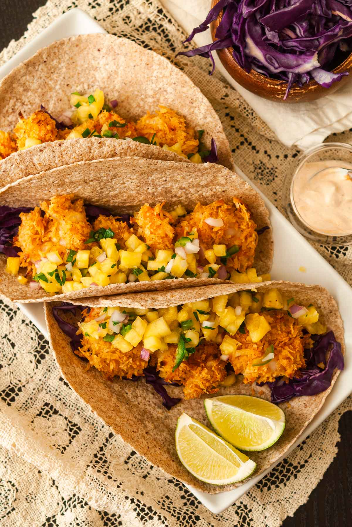 3 coconut shrimp tacos on a plate with pineapple salsa beside 2 lime slices, on a lace tablecloth.