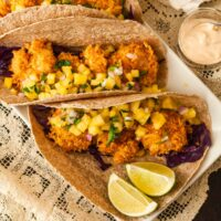 2 coconut shrimp tacos on a lace table cloth table garnished with pineapple salsa with a side of 2 lime slices.