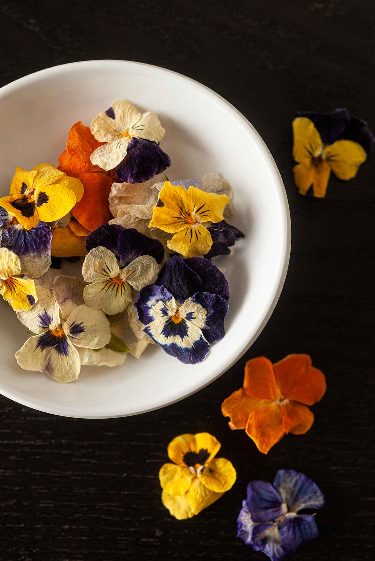 A bowl of small, dry pansies with a few flowers scattered around the bowl.