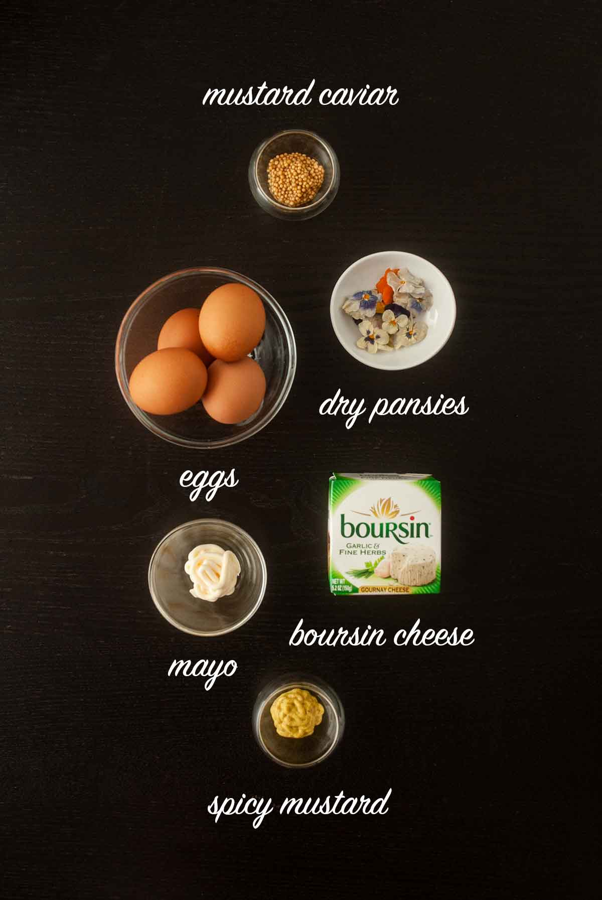 6 ingredients for making deviled eggs on a dark table with titles describing what they are.