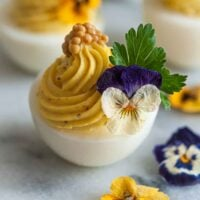 1 deviled egg on marble, garnished with flowers, cilantro and mustard caviar beside 3 scattered flowers.