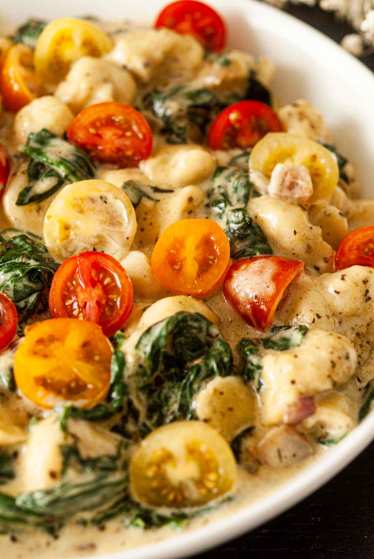 A bowl of colorful gnocchi with tomatoes and spinach in a bowl.