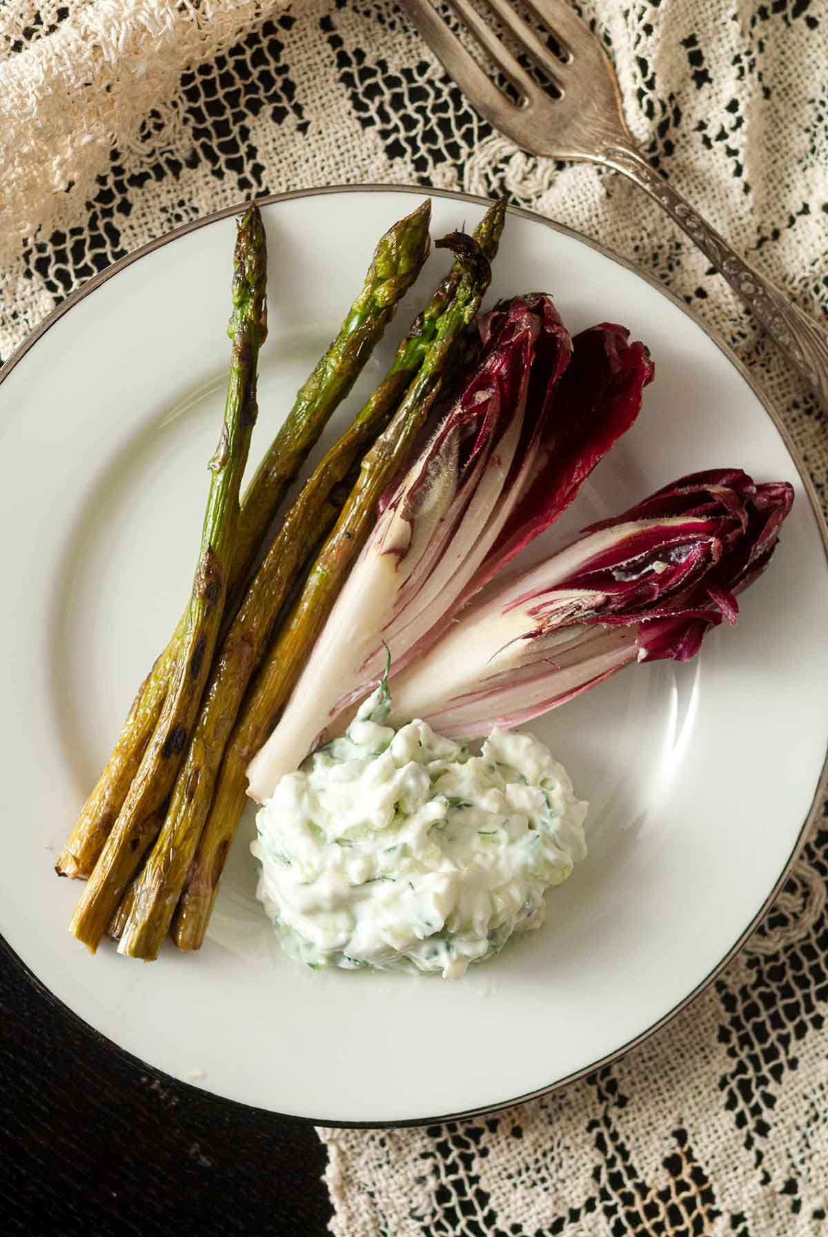 A plate with 2 sliced endive, 4 asparagus and a small pile of tzatziki.