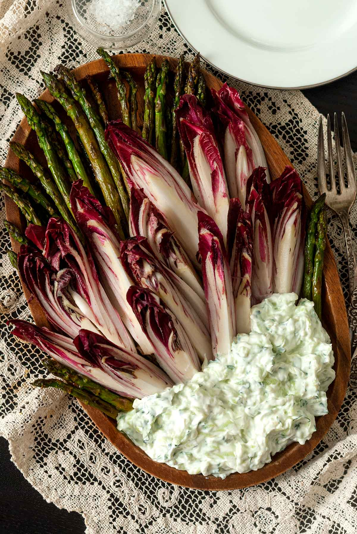 Endive and asparagus on a plate with a pile of tzatziki on a table cloth beside forks and plates.