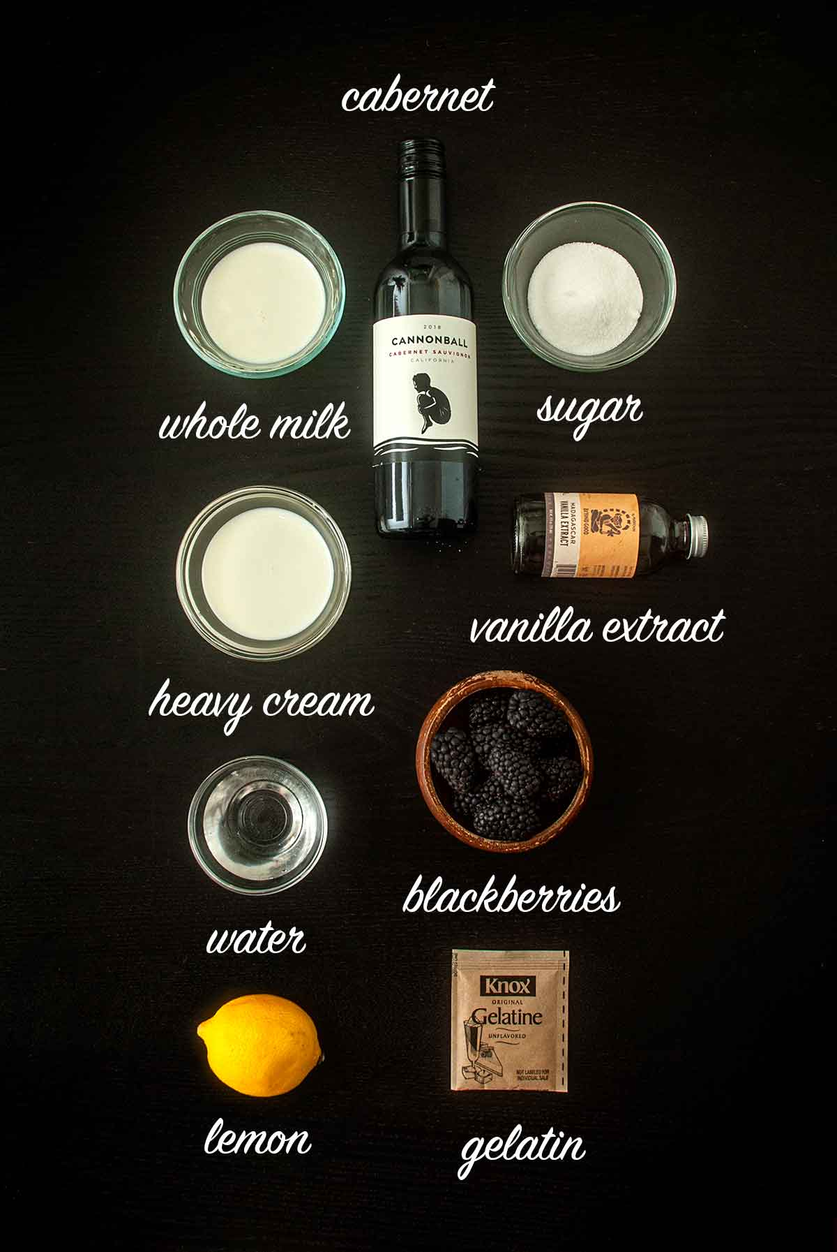 9 ingredients on a table for making panna cotta and berry sauce, with titles describing them.