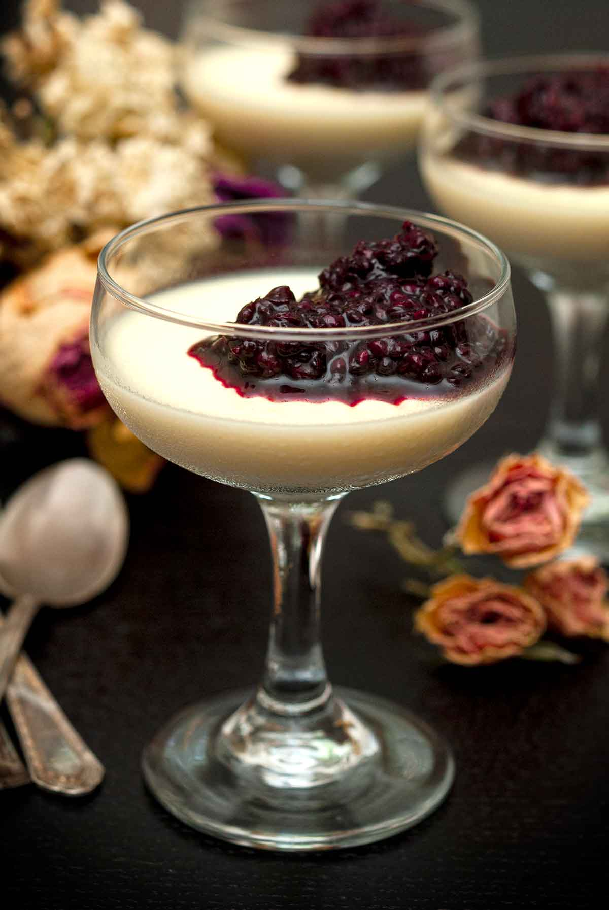 3 glasses of panna cotta with berry sauce on a table with flowers and spoons.