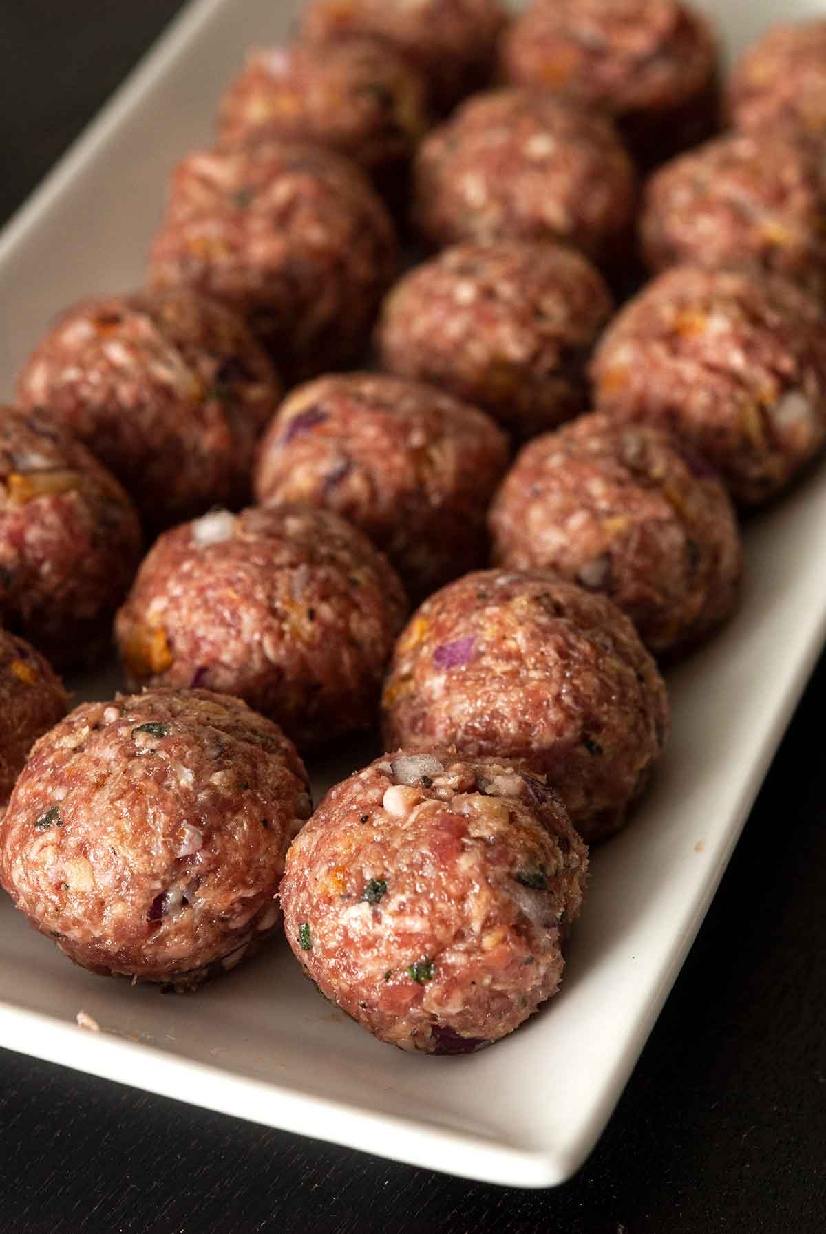 15 raw meatballs lined up on a rectangular plate.