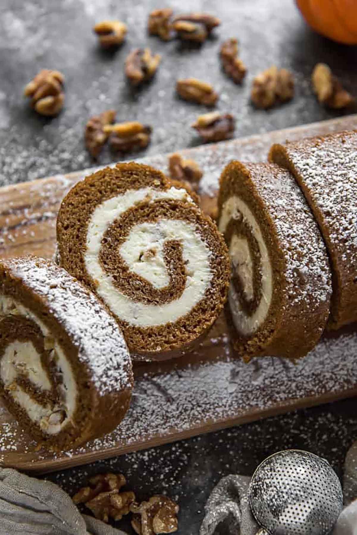 A sliced pumpkin roll on a wooden board, sprinkled with sugar.