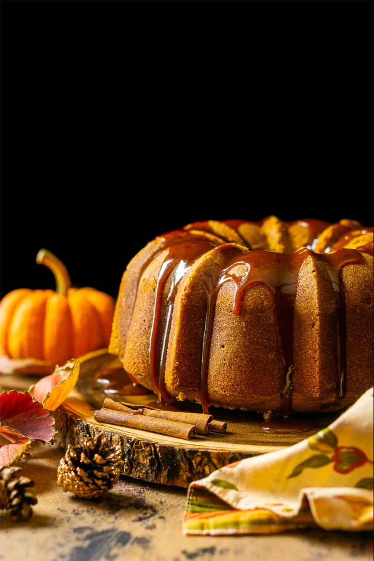A pumpkin cake on a wooden table beside a small pumpkin and scattered pinecones.