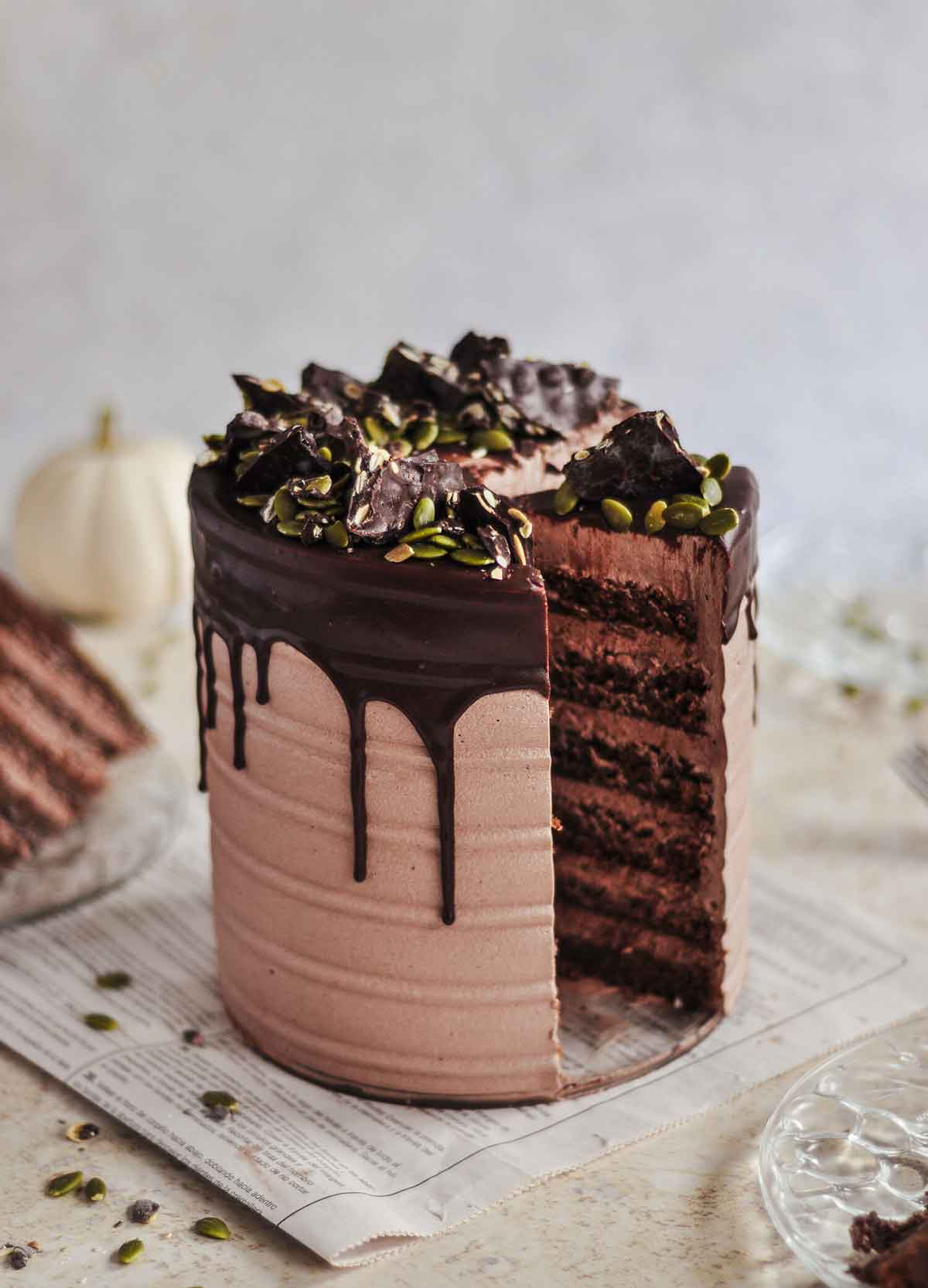 A layered cake, drizzled with chocolate, on a table with a white pumpkin in the background.