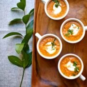 4 cups of pumpkin soup on a wooden tray on a table, beside a sprig of leaves.