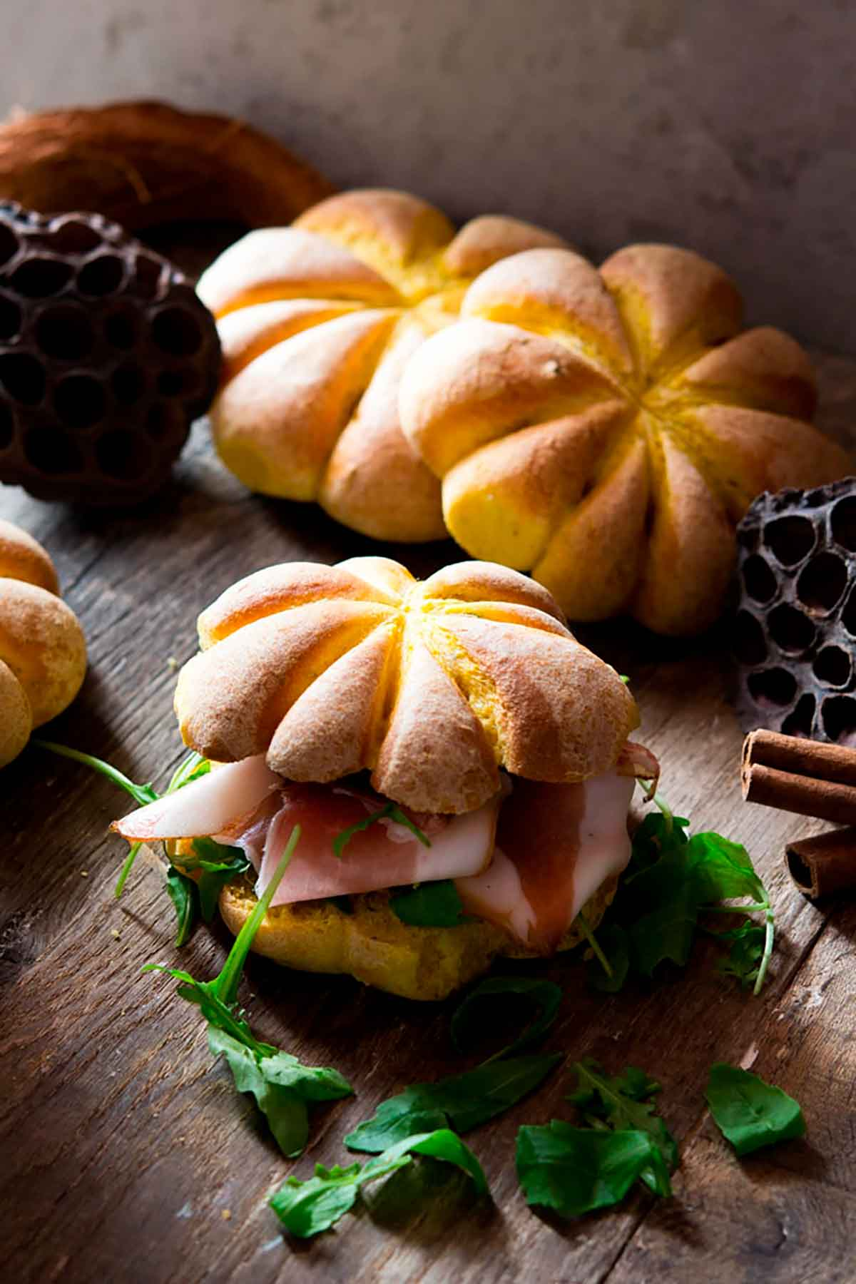 A small sandwich topped with a pumpkin roll on a table, with 2 pumpkin rolls in the background.