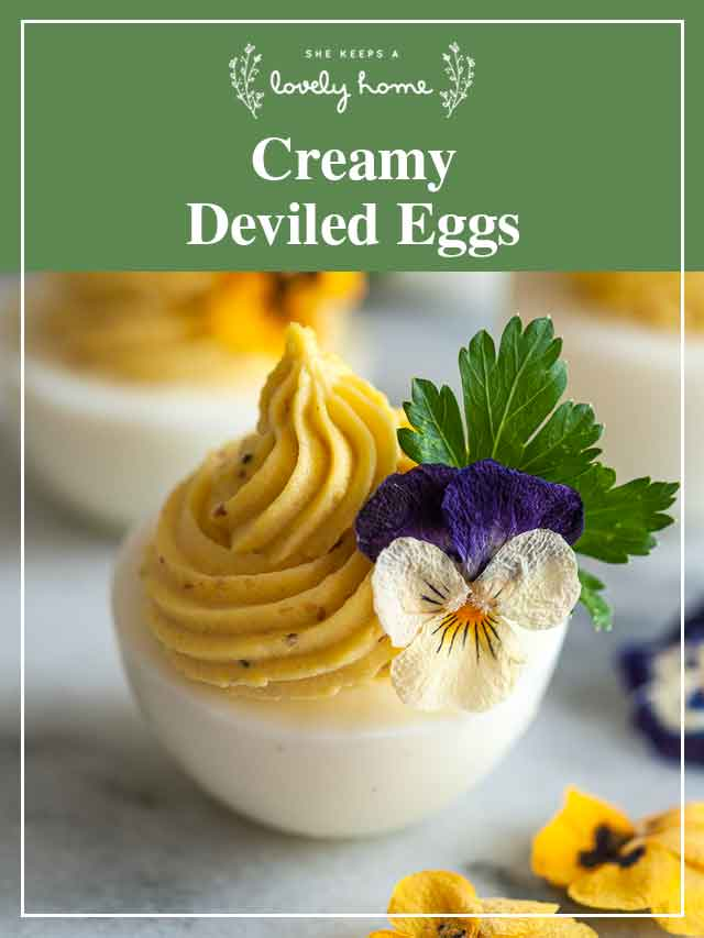 """A deviled egg garnished with flowers with a title that says """"Creamy Deviled Eggs."""""""