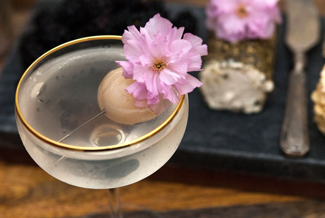 A closeup of a lychee cocktail garnished with a lychee and cherry blossom in front of a cheese plate.
